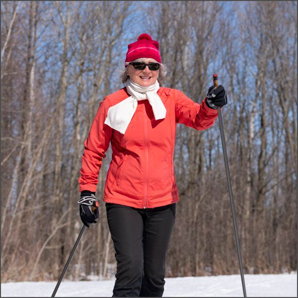 Lady in red outfit cross-country skiing